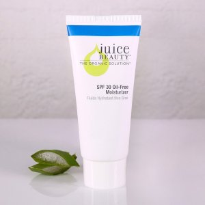 Juice Beauty Oil free SPF 30 Moisturizer on a white table  with a few green leaves to the left of the standing bottle.